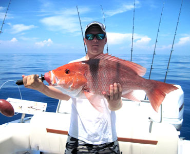 Young man holding a large red fish on a boat in Florida